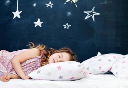 Bambina che dorme con parete di stelle.