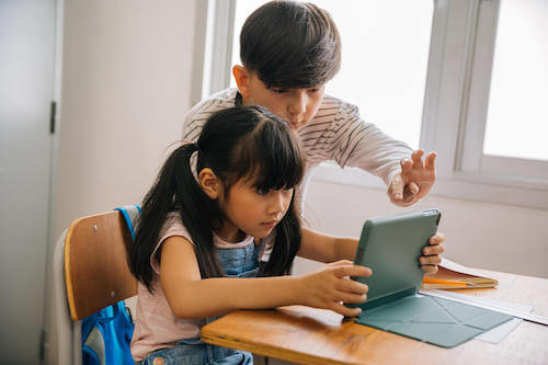 Bambini che usano un tablet per cercare informazioni su internet.