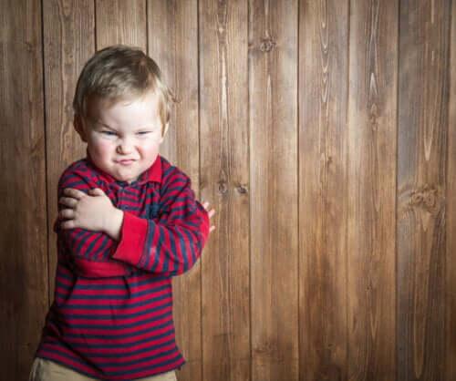 Bambino arrabbiato con maglietta a righe.