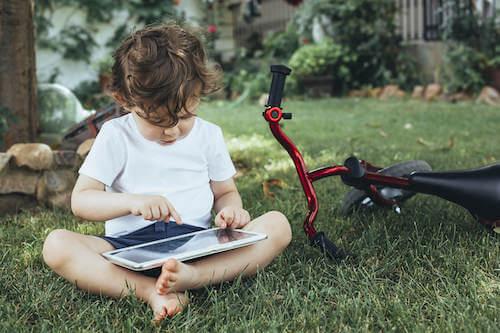 Bambino seduto sul prato del giardino di casa che usa il tablet.