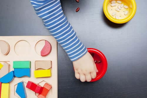 Bambino che gioca con le tavole Montessori.