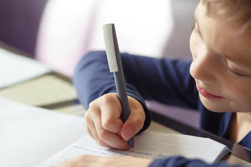 Bambino che scrive delle frasi su un quaderno per migliorare l'ortografia.
