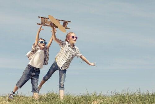 Con gli occhi di un bambino. Bambini che giocano con un aereoplanino di cartone.