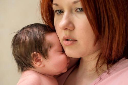 Donna triste e pensierosa che tiene in braccio il figlio neonato.