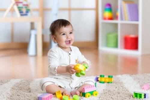 Giochi per le abilità motorie. Bambino con giocattoli sul tappeto.