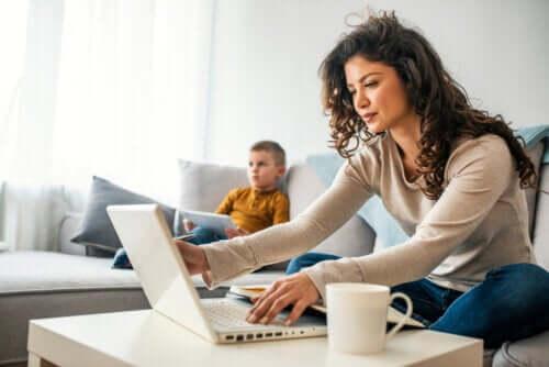 Madre che lavora mentre il figlio guarda la televisione.