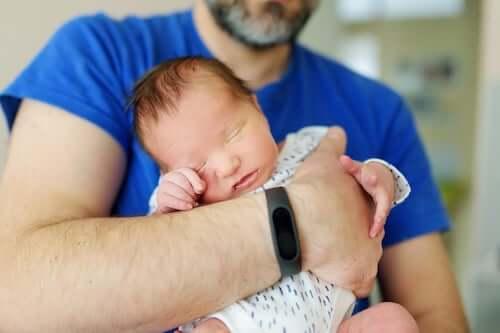 Papà che tiene in braccio il figlio appena nato.