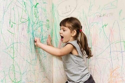 Bambina che scarabocchia sui muri.