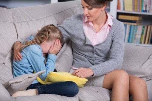 Bambina che piange sul divano con sua madre che la conforta.