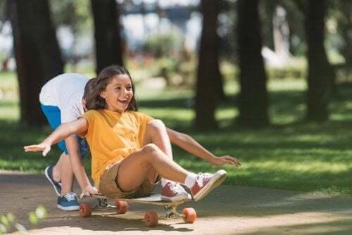 Bambini che giocano con una tavola da skate.