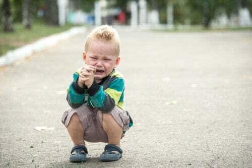Bambino sensibile che piange in strada.