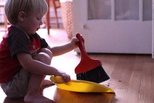 Bambino che spazza il pavimento come parte delle sue faccende quotidiane.