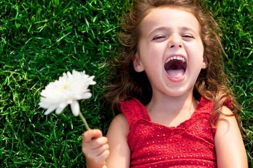Bimba che sorride con fiore in mano.