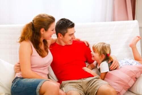 Genitori che parlano con la figlia sul divano.