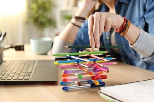 Adolescente annoiato che gioca con le penne invece di fare i compiti.