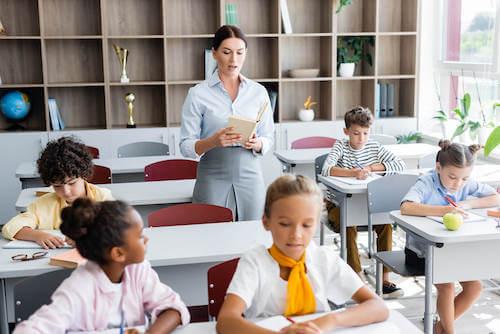 Alunni che fanno un dettato in classe.
