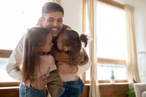 Padre che abbraccia le figlie.