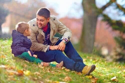 Padre che parla con suo figlio piccolo di cose difficili nel parco.